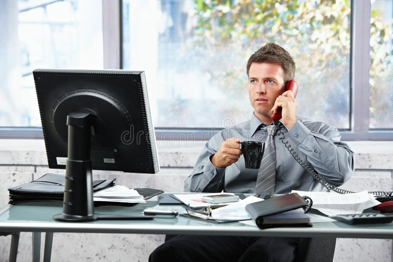 Businessman calling at office with mug royalty free stock images
