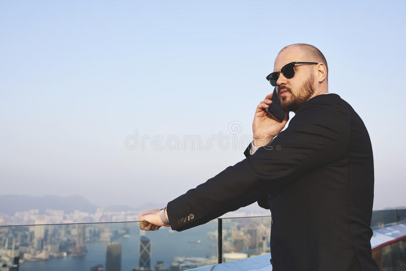 Businessman is calling via mobile phone, while is standing on building roof against city view with copy space. Young man skilled managing director having cell royalty free stock photos