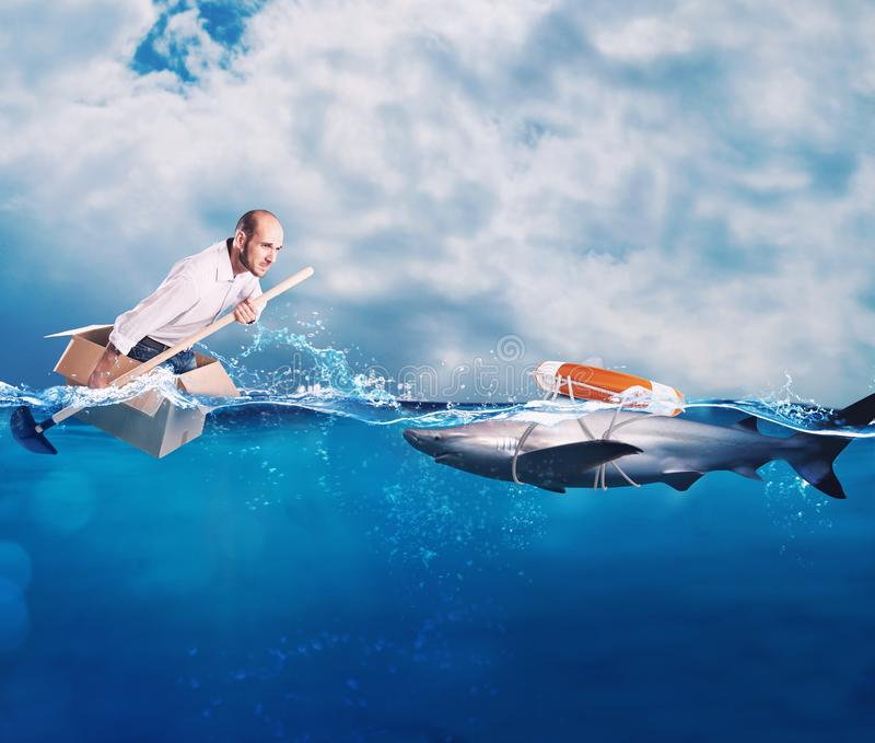 Businessman on a cardbox in the ocean looks for an help. Help with deception concept. Businessman on a cardbox in the ocean looks for an help of a lifebelt. Help stock photography