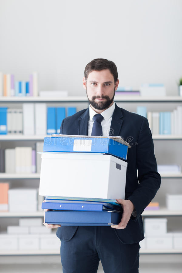 Businessman carrying a box and office folders stock photography