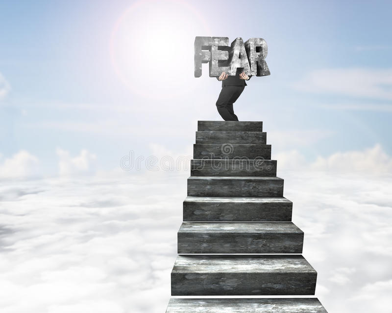 Businessman carrying fear concrete word on top of concrete stair. Businessman carrying big 3D fear concrete word on top of concrete stairs, with sky sun clouds stock images