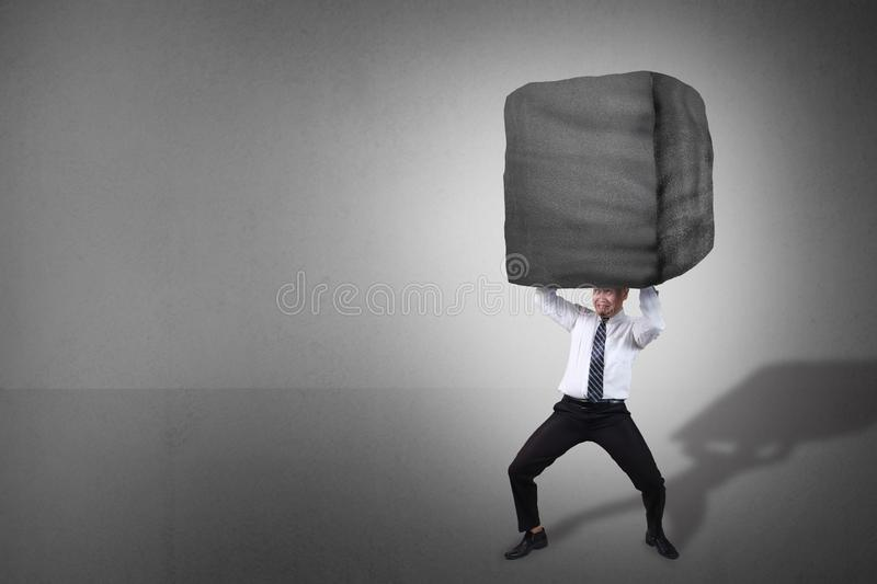 Businessman Carrying Heavy Stone. Composite image. Stress overwork and pressure in business concept. Businessman holding heavy stone over his head. Grunge stock photography