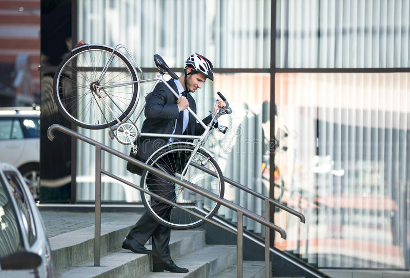 Businessman carrying his bike. Businessman with a cycle helmet on head carrying his bike down steps royalty free stock photography