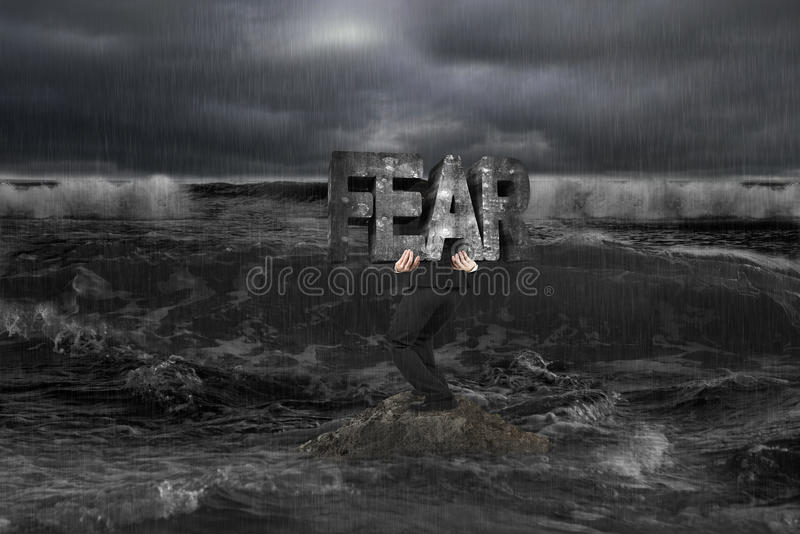 Businessman carrying old structure of FEAR on rock in dark ocean. Businessman carrying old concrete structure of FEAR on rock in dark ocean stock photo