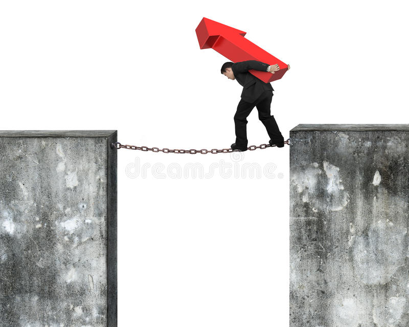Businessman carrying red arrow sign balancing on rusty chain. Connected two high dirty concrete walls, with white background royalty free stock photography