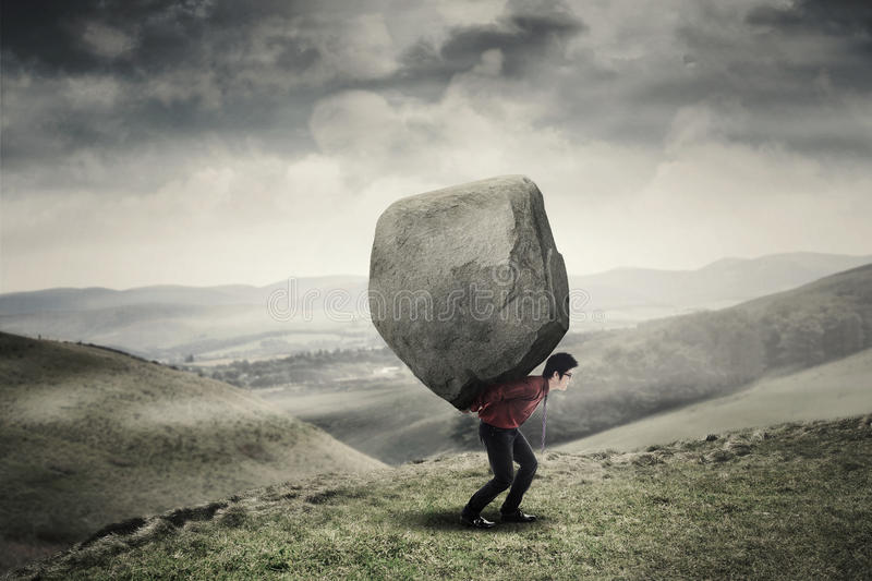Businessman carrying rock at hill stock photography