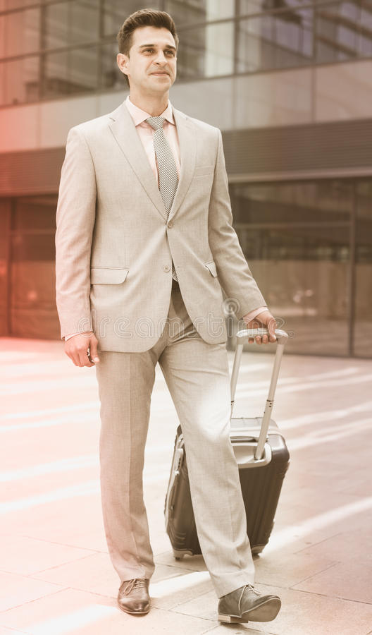 Businessman carrying suitcase royalty free stock photos