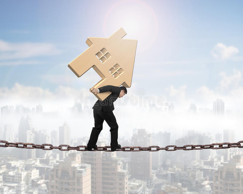 Businessman carrying wooden house balancing on chain stock image