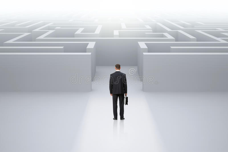 Businessman with case standing in front of maze royalty free stock image