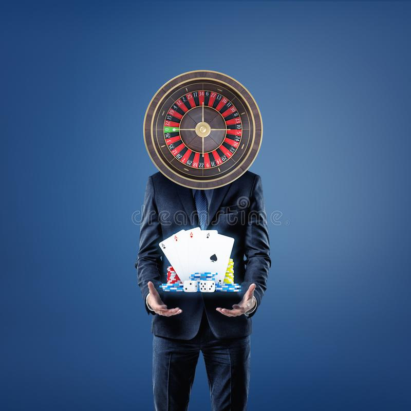 A businessman with a casino roulette instead of his head stands and offers cards, dice and casino chips. stock images