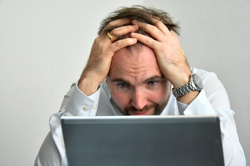 Businessman looks horrified at his computer. Businessman casually dressed works in his office. He is appalled by what he sees on the computer screen stock photography