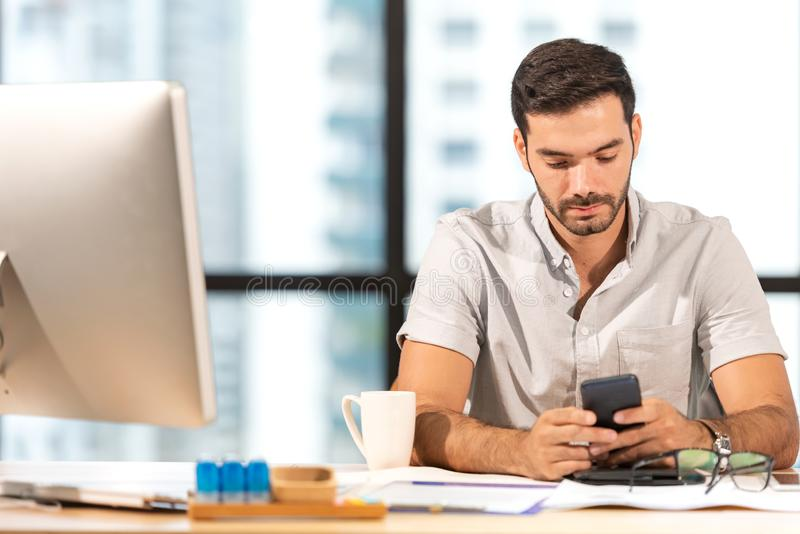 Businessman caucasian using  mobile to work with financial data in the modern office, relax and rest time after work. stock photography