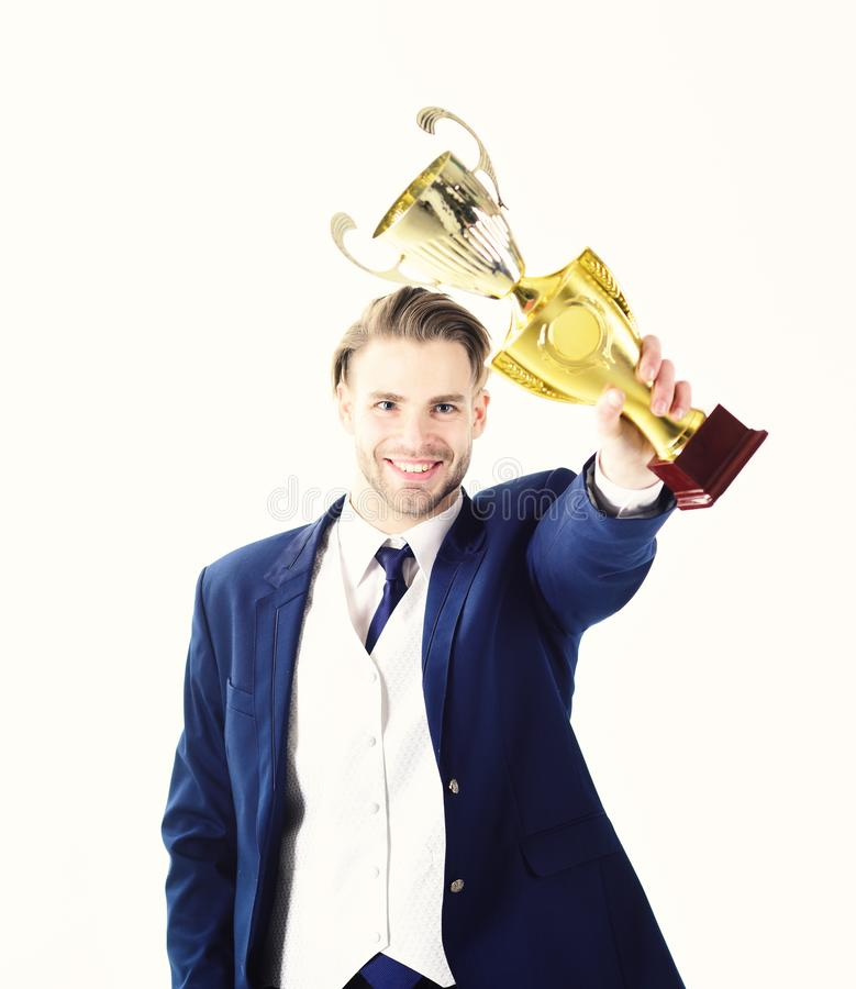 Businessman celebrates successful start up. Winner holds trophy and smiles. Guy with happy face shows trophy. Man in stock photos