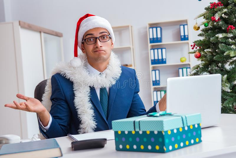 Businessman celebrating christmas holiday in the office. The businessman celebrating christmas holiday in the office stock photos