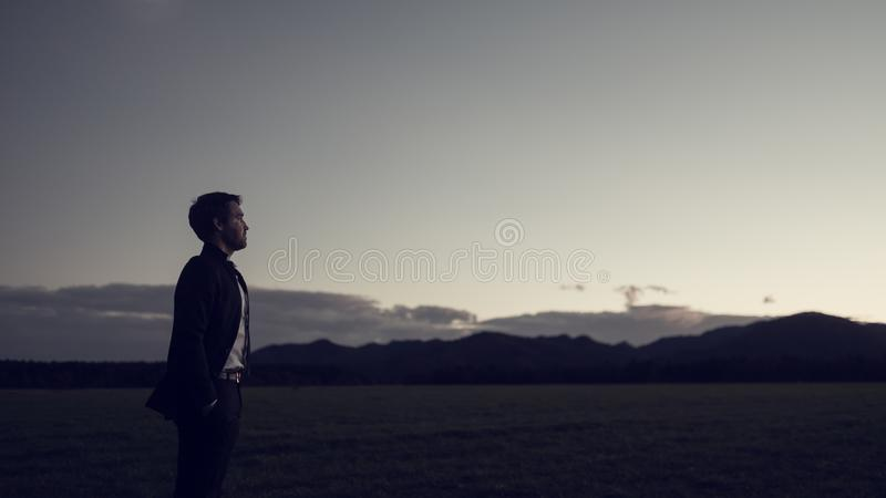 Businessman celebrating a new day standing in his business suit. Outside in nature as the sun peeps over the distant mountains, retro toned image royalty free stock photo