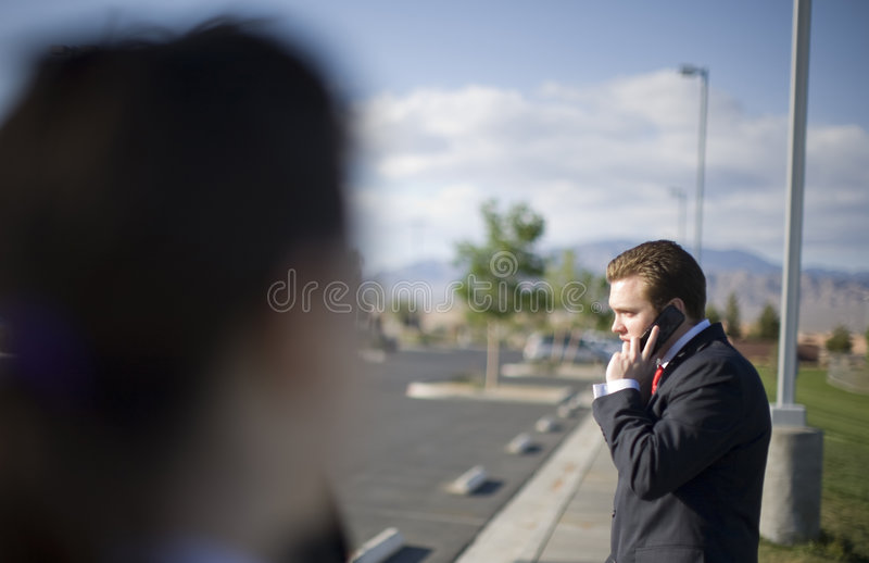 Businessman on cell phone. A businessman is talking on his cell phone wearing a dark suit standing outside with other business people looking at him royalty free stock image
