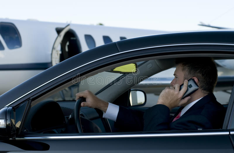 Businessman on cell phone in luxury car stock image
