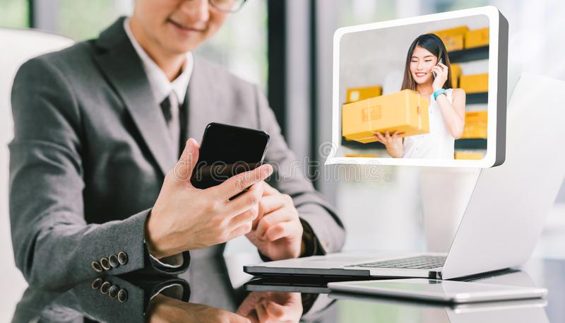 Businessman CEO order product box from young female Asian small business owner using phone, laptop. E-commerce technology concept. Businessman CEO order product royalty free stock photo