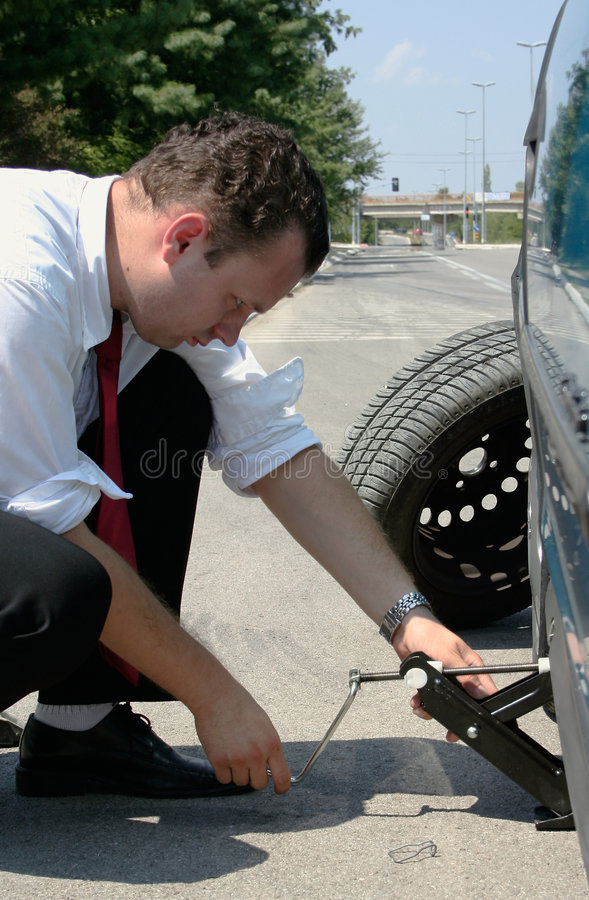 Businessman changing a tire stock images