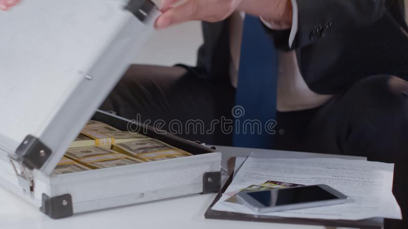 Businessman checking money in briefcase, kickback for politician, close up royalty free stock photo