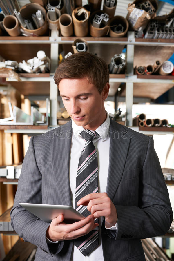 Businessman Checking Stock In Warehouse Using Digital Tablet. Businessman Checks Stock In Warehouse Using Digital Tablet royalty free stock image