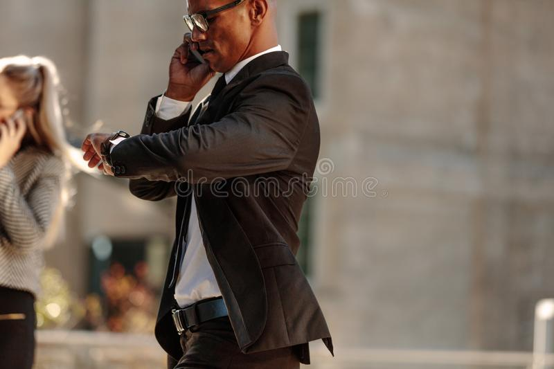 Businessman checking time while going to office stock photo