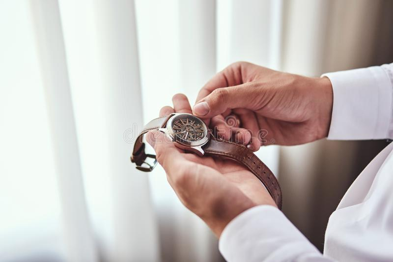 Businessman checking time on his wrist watch, man putting clock on hand,groom getting ready in the morning before wedding ceremony. Businessman checking time on royalty free stock image