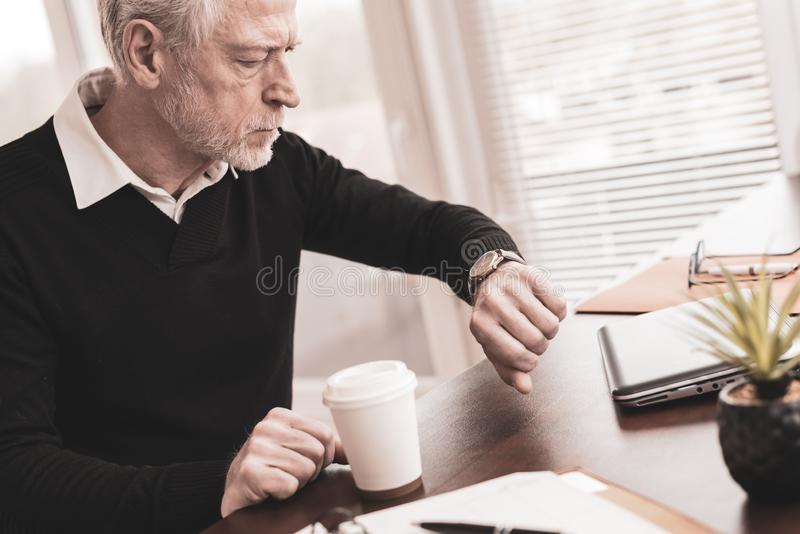Businessman checking time on his wrist watch royalty free stock image