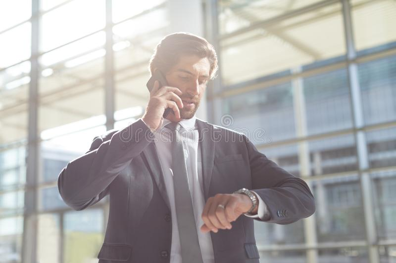 Businessman checking time while talking on mobile phone in lobby office stock photo