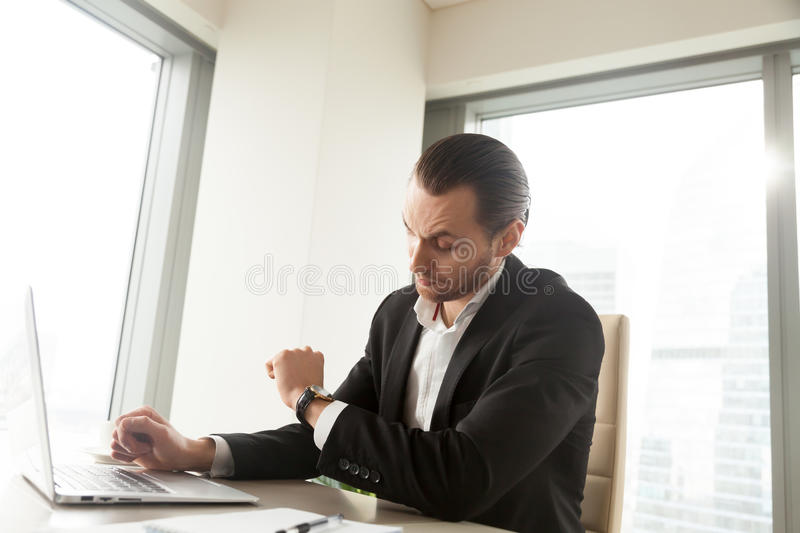 Businessman checks time left to important meeting. Office worker at desk looking at wristwatch, waiting for the end of work day. Busy young entrepreneur hurrying stock images