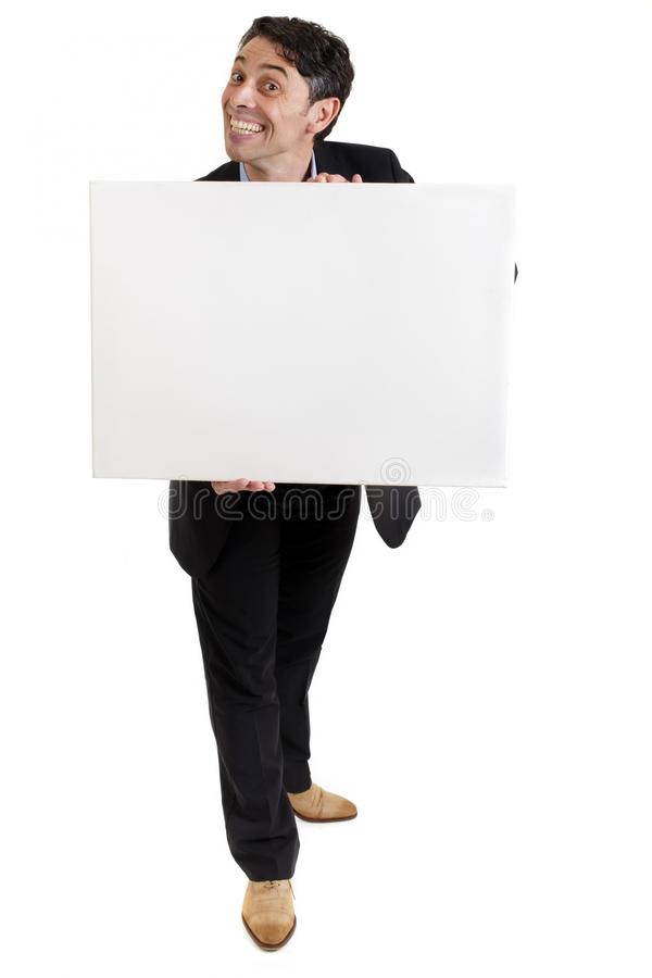 Businessman with a cheesy grin. Smart, middle-aged businessman with a cheesy insincere toothy grin holding a blank white sign in his hands with copyspace for stock photography