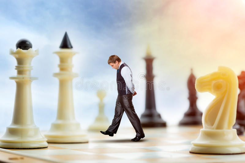 Businessman on the chess board. Businessman is walking on the chess board thinking royalty free stock images