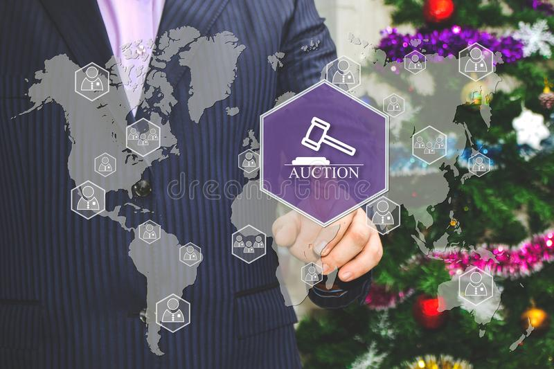 The businessman chooses AUCTION on the touch screen, the backdrop of the Christmas tree and decorations. Special toning stock images