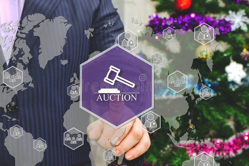 The businessman chooses AUCTION on the touch screen, the backdrop of the Christmas tree and decorations. Special toning royalty free illustration