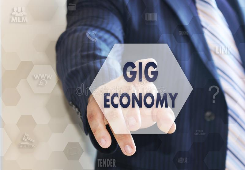 The businessman chooses the GIG ECONOMY on the touch screen.  stock image