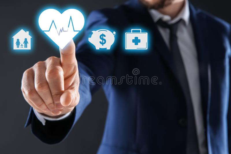 Businessman choosing heart icon on virtual screen against dark background. Life and health insurance royalty free stock photography