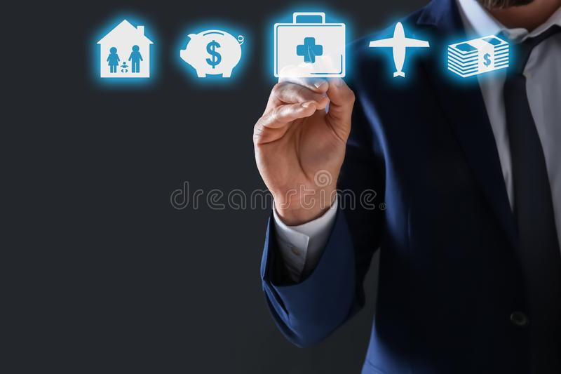 Businessman choosing icon on virtual screen against dark background. Life and health insurance royalty free stock photos