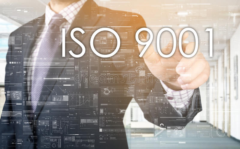 The businessman is choosing ISO 9001 from touch screen. The businessman is choosing text from virtual touch screen royalty free stock images