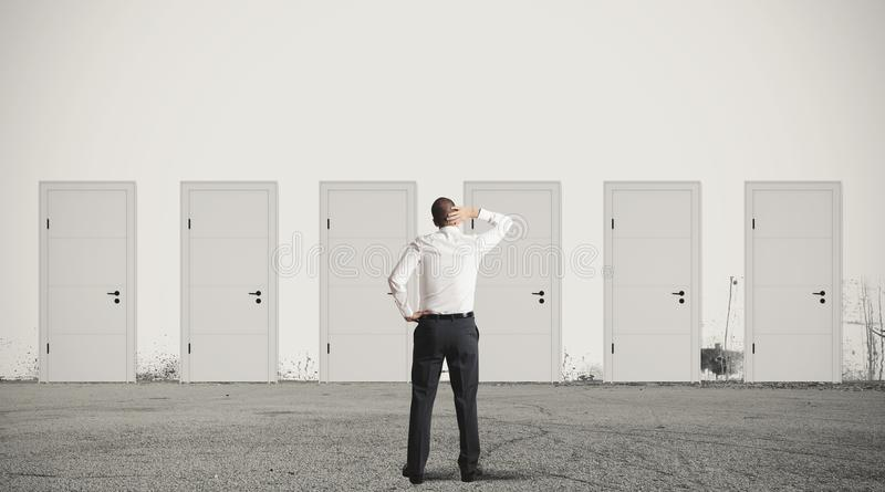 Businessman choosing the right door stock photography
