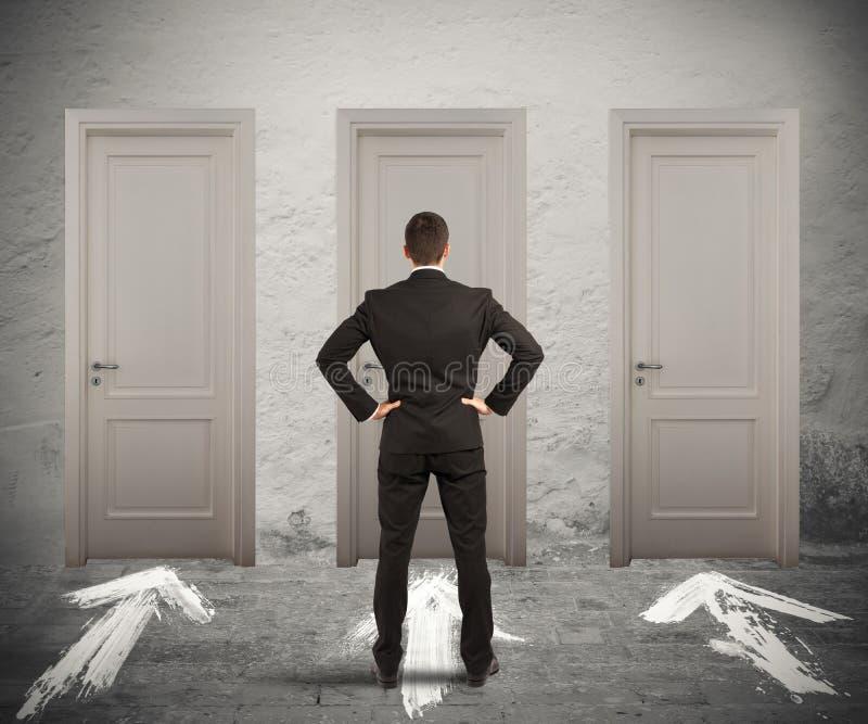 Businessman choosing the right door royalty free stock photos