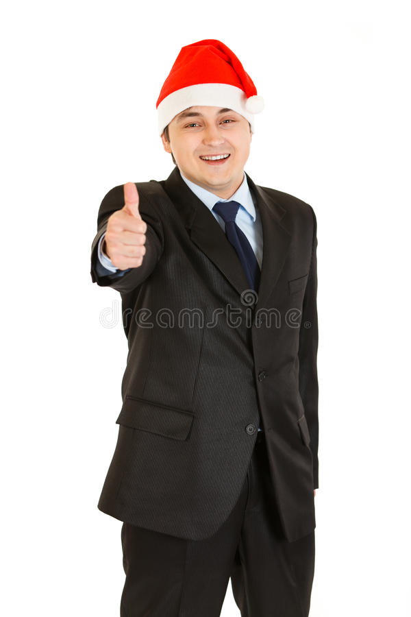 Businessman in Christmas hat showing thumb up royalty free stock photography