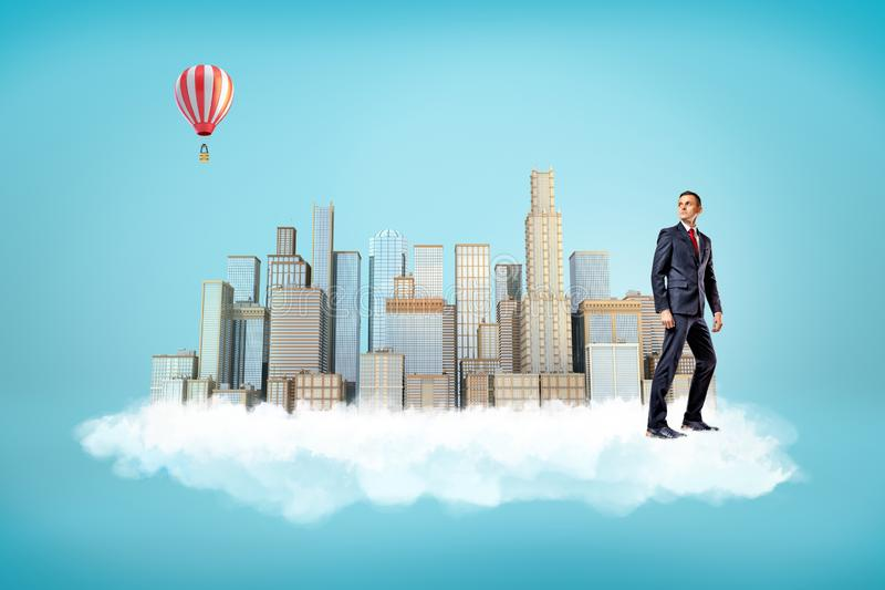 Businessman with city skyscrapers on white cloud and hot air balloon in the air on blue background royalty free stock image