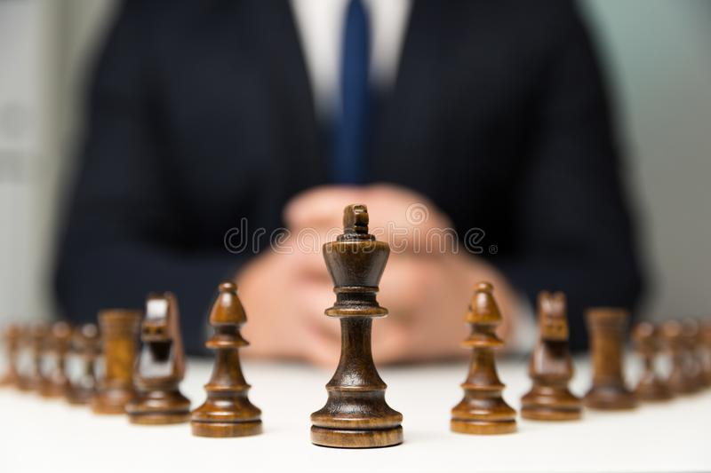 Businessman with clasped hands planning strategy with chess figures on table. Strategy, leadership and teamwork concept. stock photography