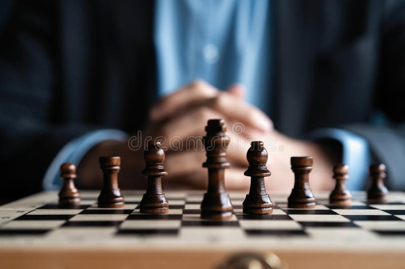 Businessman with clasped hands planning strategy with chess figures on table. Strategy, leadership and teamwork concept. royalty free stock photography