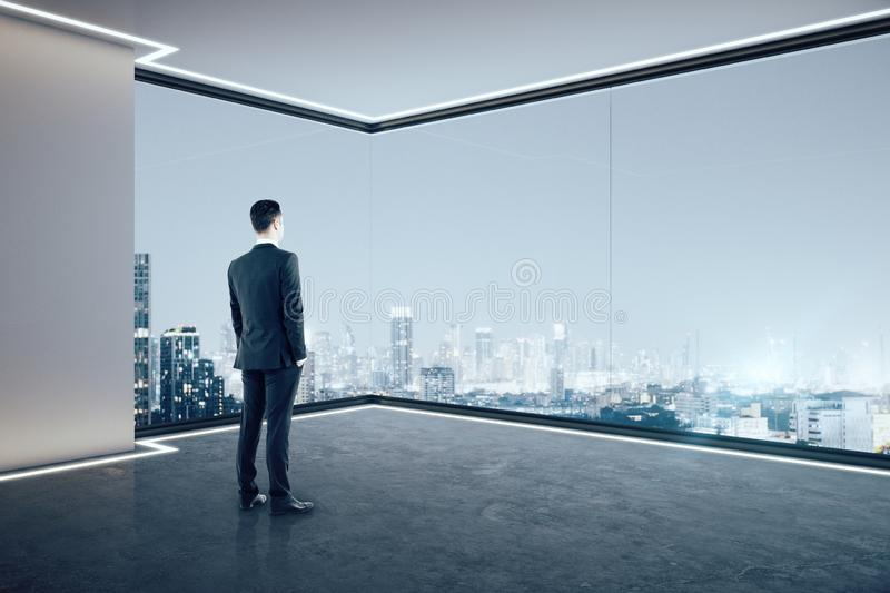 Businessman in clean office. Businessman looking out of window in clean empty spacious office interior with illuminated panoramic city view. Research concept stock photography