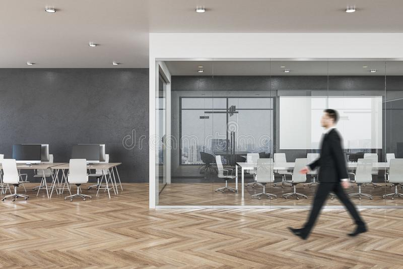 Businessman in clean office. Side view of blurry businessman walking in clean spacious office room interior with city view and daylight. Executive concept royalty free stock image