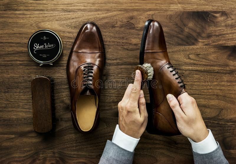 Businessman cleaning his shoes with a brush stock photos