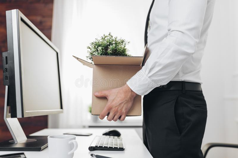 Businessman clearing his desk after being made redundant. Dissapointed businessman clearing his desk after being made redundant royalty free stock images