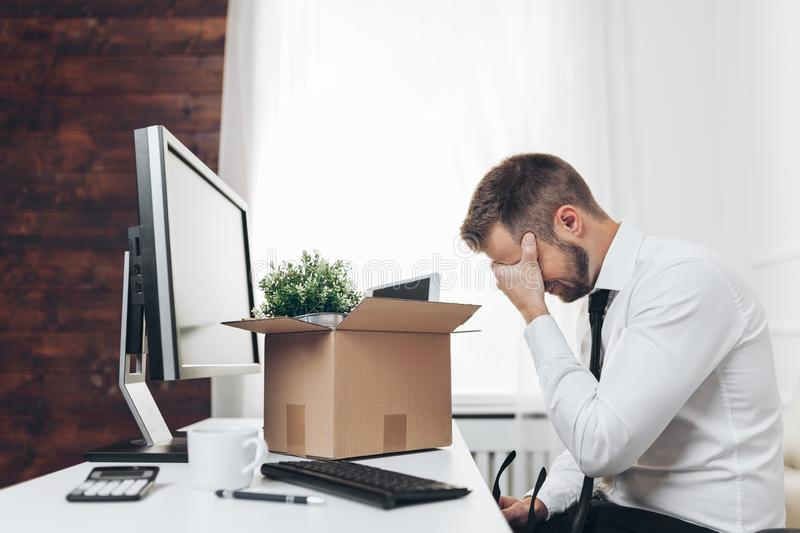 Businessman clearing his desk after being made redundant. Dissapointed businessman clearing his desk after being made redundant royalty free stock photography