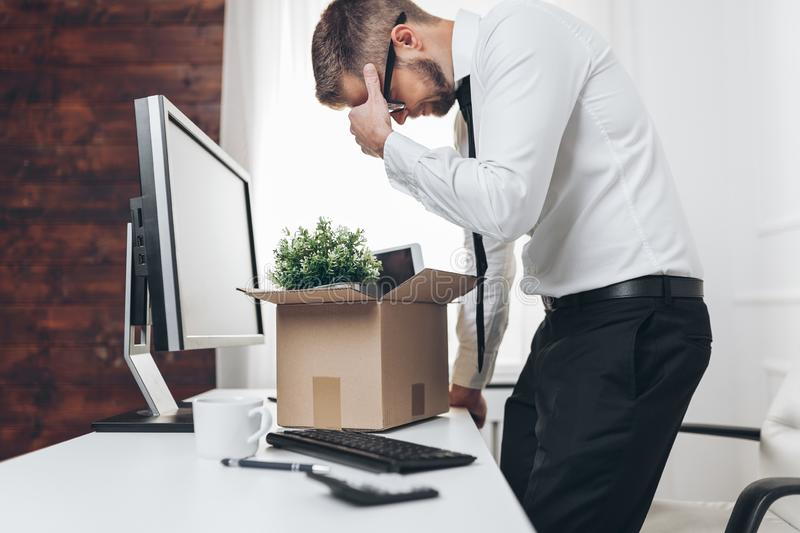 Businessman clearing his desk after being made redundant. Dissapointed businessman clearing his desk after being made redundant royalty free stock photos